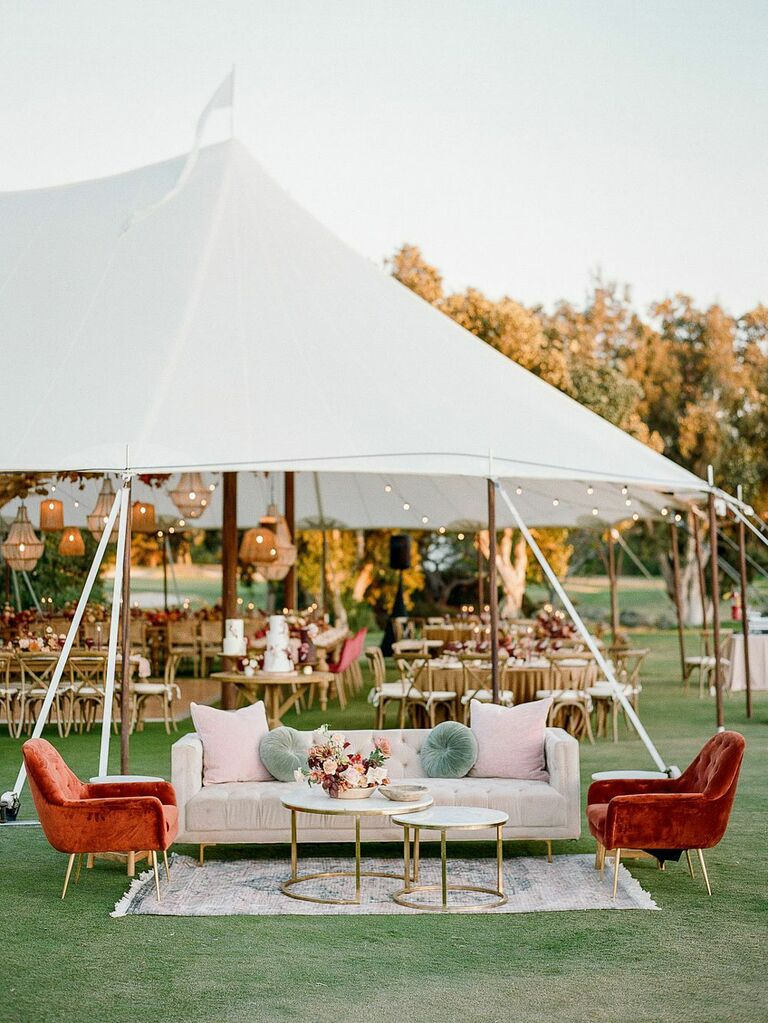 Vibrant seating area in front of white outdoor wedding tent