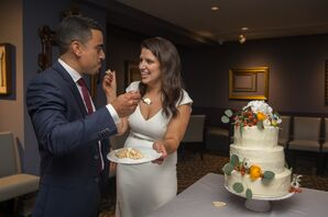 Couple Cutting Into Round, Tiered Cake with Berries and Flowers