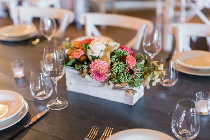 Loosely arranged bundles of dahlias, roses, hydrangeas moss and wildflowers in antiqued wooden planters brought a pop of color to the charming farm tables that filled the rec hall during the reception.