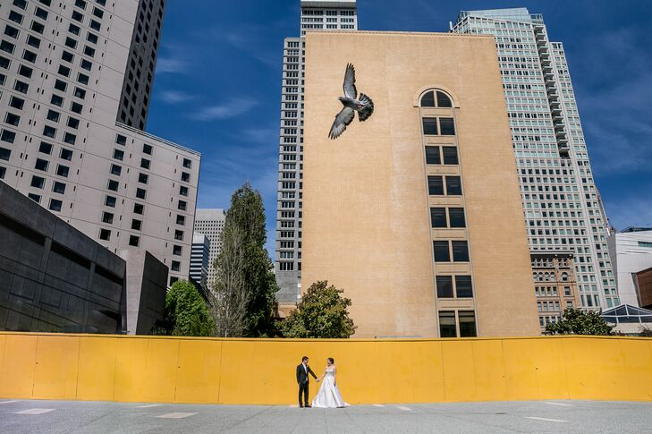 Chelsea and Chris stood outside against a yellow wall backdrop, with the city of San Francisco, California, surrounding them. Chelsea and Chris knew they wanted their venue to highlight the city, where Chelsea lived throughout their engagement.