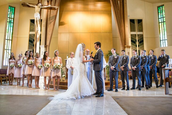 """Christina and Kyle were married at St. Maximilian Kolbe Catholic Church in Westlake Village, California, where they stood at the front of the altar surrounded by their bridesmaids and groomsmen. The bridesmaids wore knee-length light pink dresses while the groomsmen wore charcoal gray suits. """"We had our wedding at one of the most stunning churches we had ever seen,"""" Christina says. """"It was all dark wood on the inside, which happened to go with the look of our wedding. We wrote our own wedding vows, and Kyle's two brothers performed a song for us during the ceremony, which was very special."""""""