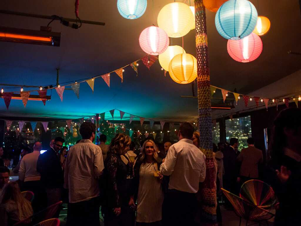 Party at nighttime on the Green Fig rooftop.