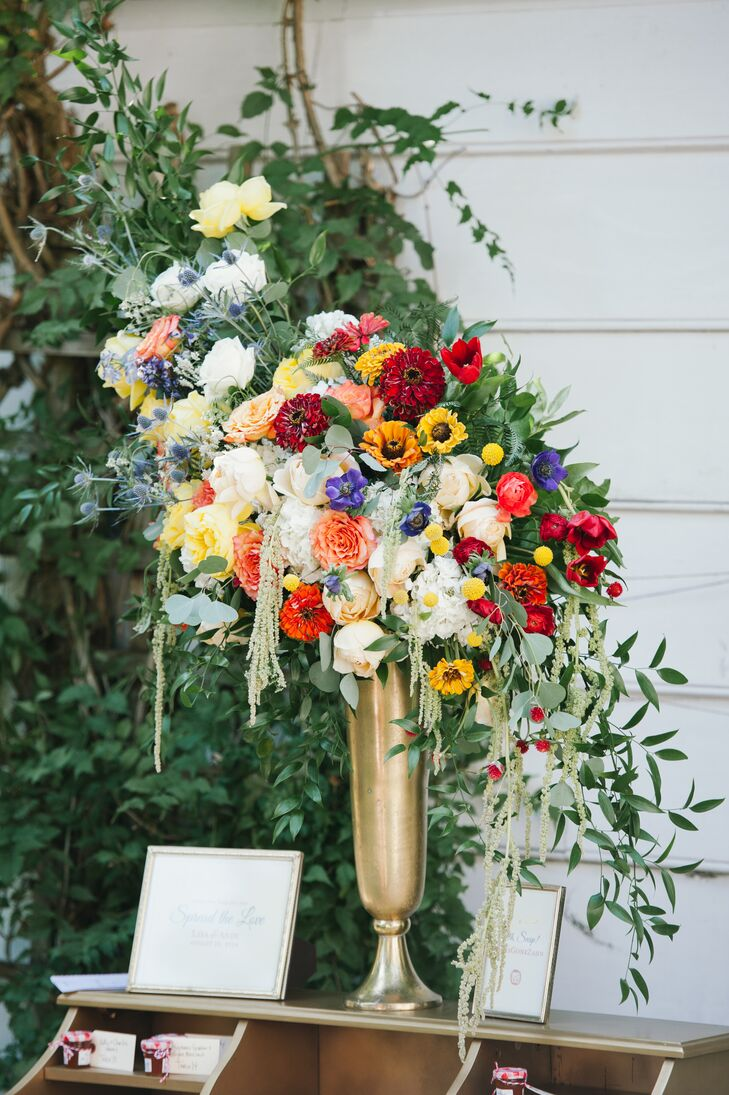 Warm colored hydrangeas, yarrows and zinnias accented with fern, seeded eucalyptus and green amaranths in a gold Milan vase were arranged by La Petite Fleur.