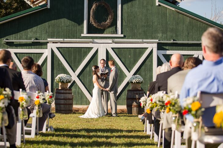 The vineyard ceremony took place in front of a green barn situated in between rows of grapevines.