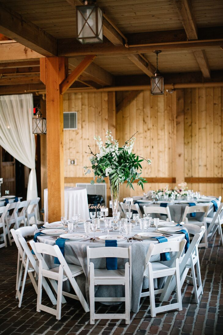 The rest of Hope and Nick's guests were seated throughout the barn at classic round tables topped with regal white and navy linens. Varying high and low centerpieces filled with lush greenery and blooms in shades of pink, white and blue added texture and drama to the decor.