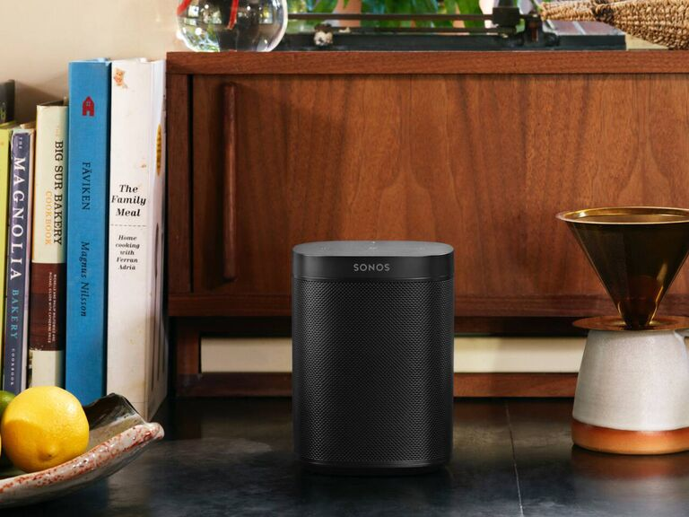 Black Sonos One speaker on counter next to fruit bowl and books
