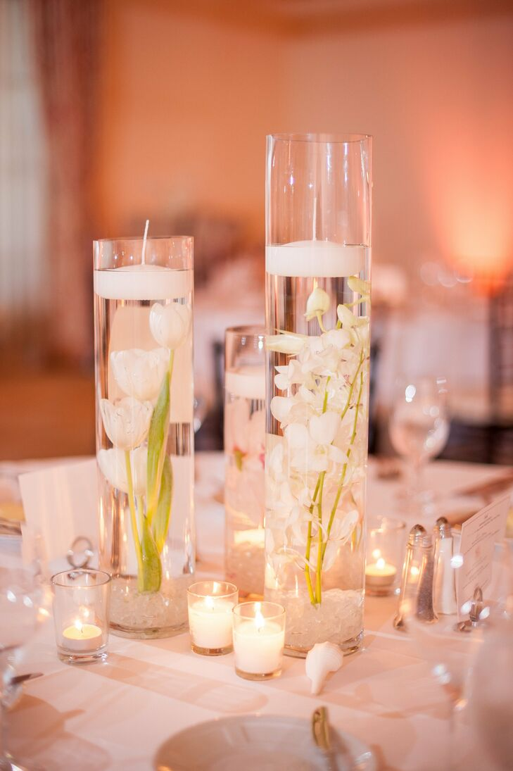 For the guests table arrangements there were 3 glass cylinder vases in different heights filled with water.  Each held a single tall white orchid, tulip, or ranunculus that had a floating candle on top and beach glass on the bottom.