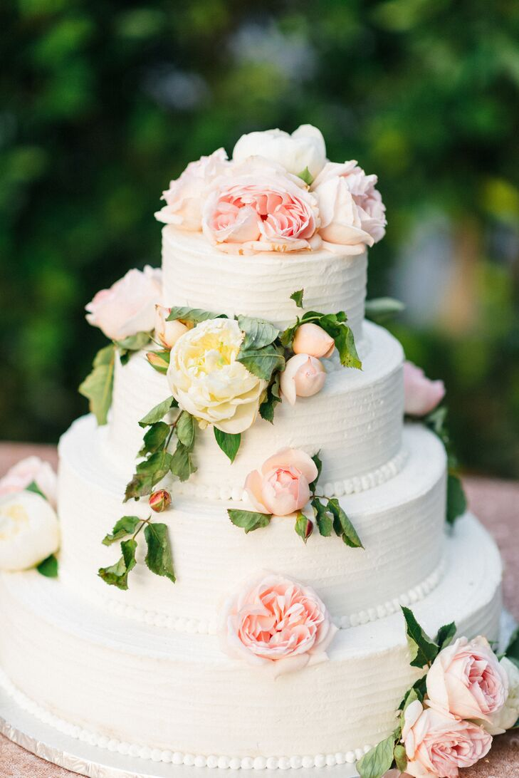 """Our cake was simple—three tiers with white whipped frosting, fresh cascading roses, peonies and greenery,"" Andrea says. ""It was chocolate with fresh whipped cream and strawberries inside—and it was consumed entirely that night."""