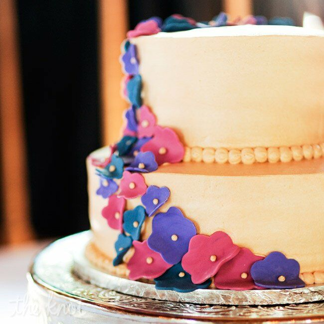 The two-tiered cake was topped with bright sugar flowers and pearl piping.