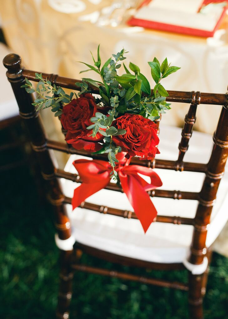 Fresh bunches of greenery and dark red roses were tied to the back of each reception chair with a simple red bow.