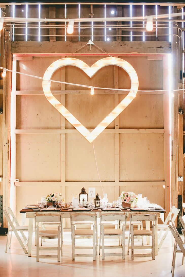 A large heart-shaped decoration hung on the wall and created a romantic glow inside the space. Wooden dining tables seated guests inside the barn, which had rustic boxes filled with pastel-colored blooms that added some rustic charm.