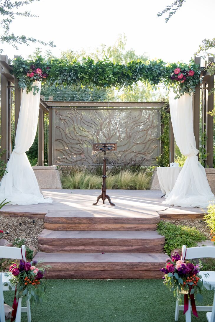 """""""We knew the Springs Preserve was the place our wedding needed to be the moment we walked in,"""" Jenna says. """"It had the botanical garden feel we wanted, and we knew the weather would be perfect in October."""" The ceremony took place at the arboretum under a greenery-rich arch."""