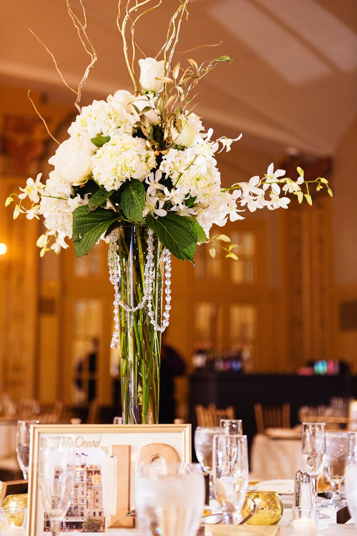 Christine and Keith decorated the reception tables with ivory hydrangeas, roses and orchids and completed the vases with gold branches and beads.