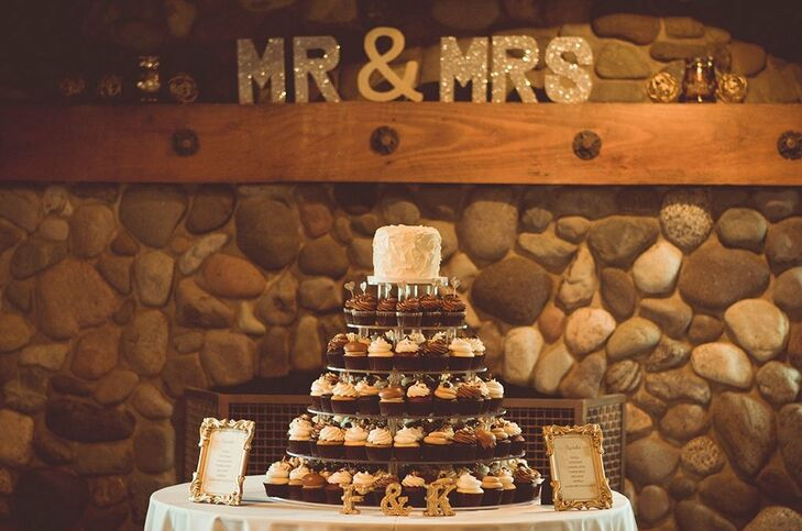 Chocolate and vanilla cupcakes were displayed on a large cupcake stand with a sweetheart cake on top as dessert.