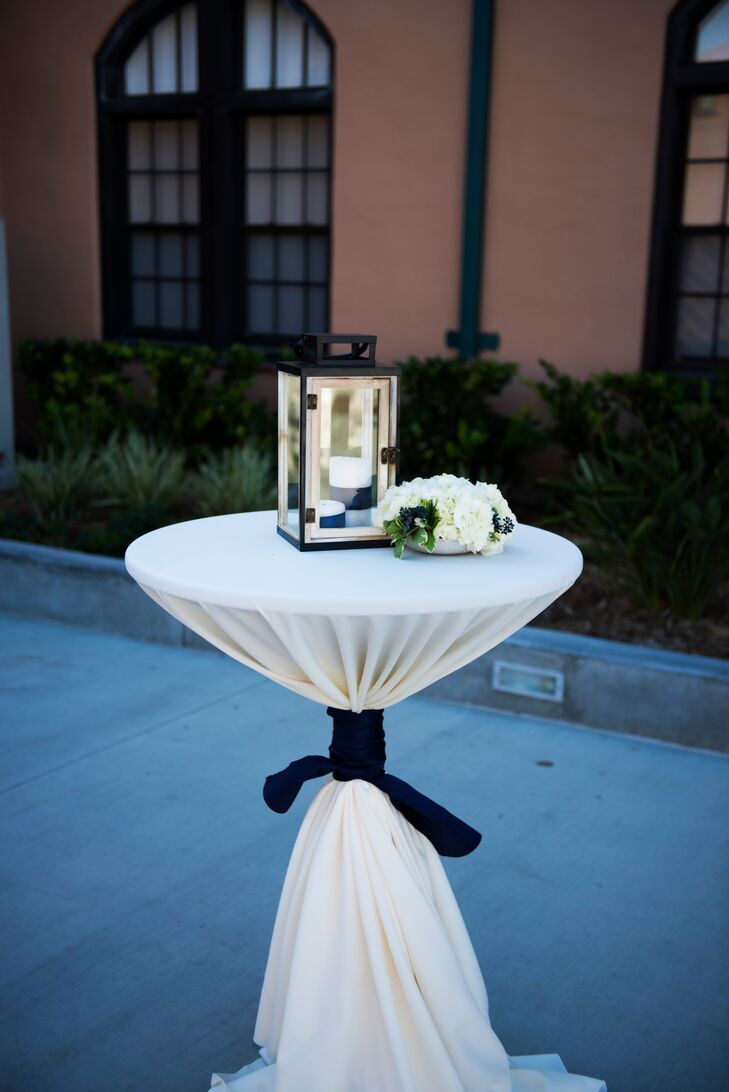 Cocktail tables dressed in white linens were decorated with black lanterns and white hydrangea flower arrangements.