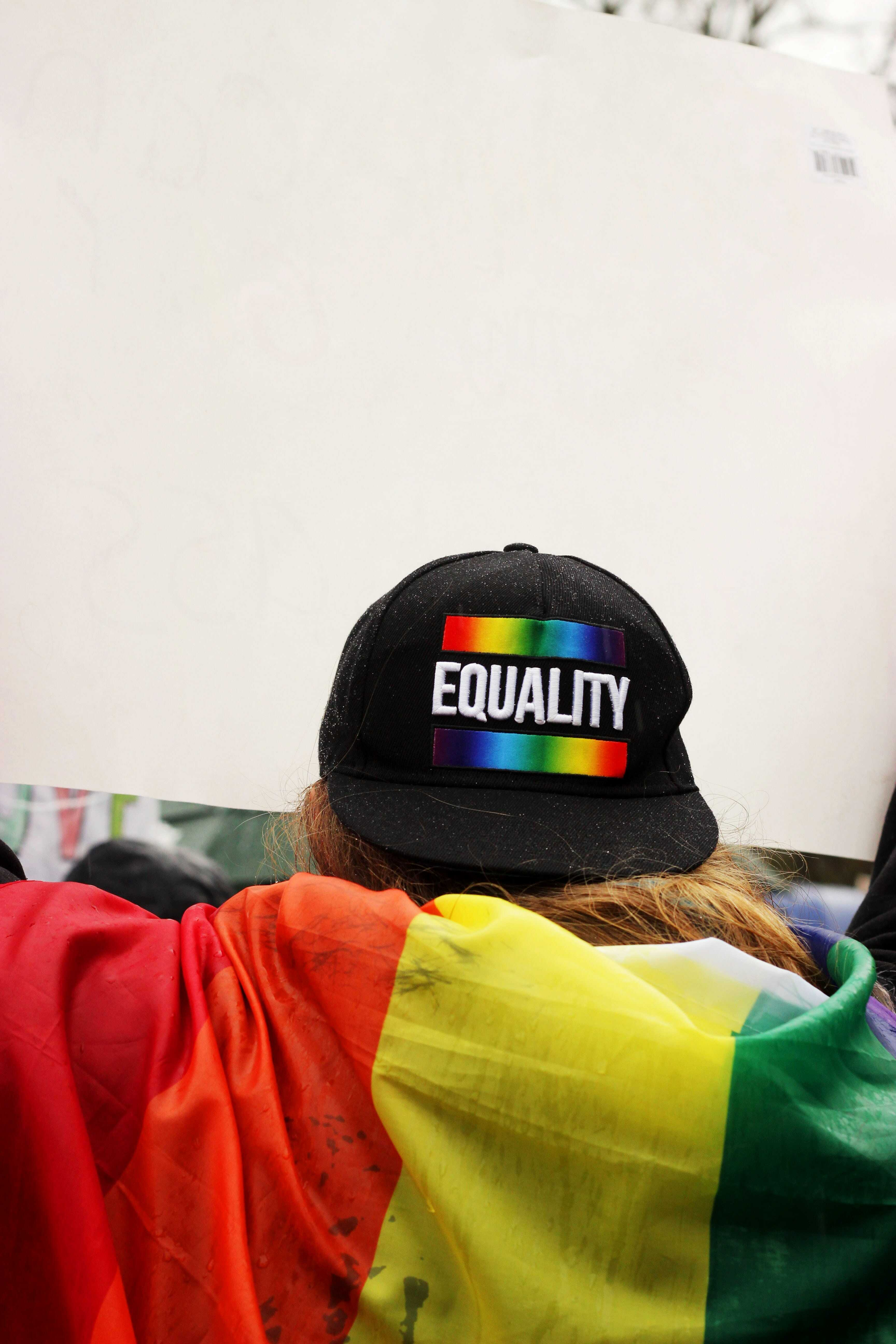 Person wearing equality hat and flag