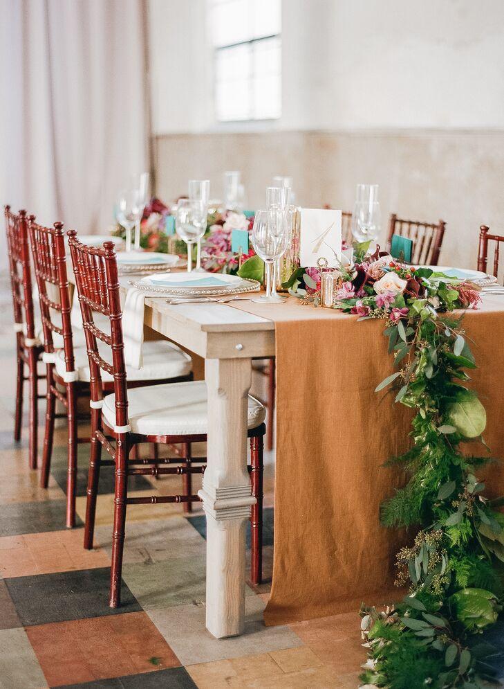 A few tables consisted of a long banquet style and featured garlands that cascaded to the floor on each end, adorned with burgundy flowers and birch candles.