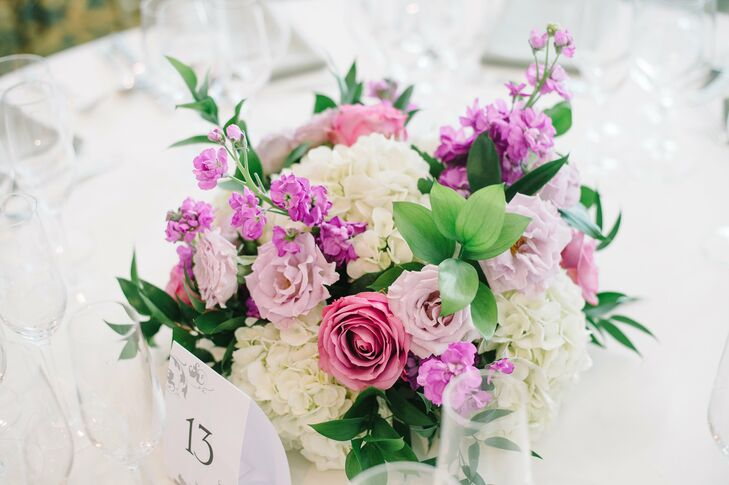 """We wanted short, simple, minimal centerpieces,"" Allison says. In keeping with the romantic garden theme, centerpieces at the reception were made up of pink roses, lavender lisianthus, purple stock, ivory hydrangeas and leafy greens."