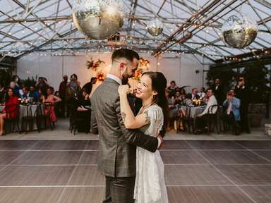 Bride and groom dancing during first dance under disco balls at reception