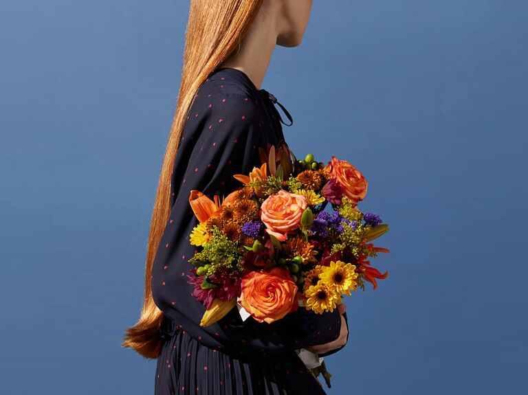 woman holding bouquet of fresh flowers