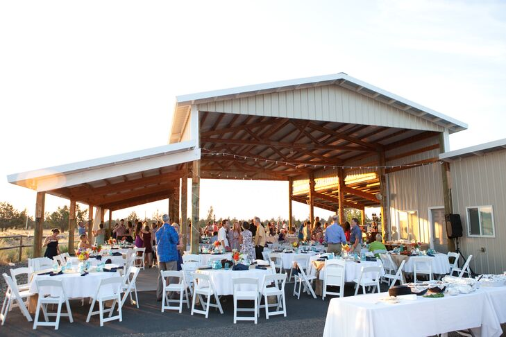 """""""We had our reception under the converted hay barn that overlooked the cascade mountain range and the fields surrounding our venue,"""" the couple says. """"The sun was just starting to set behind the mountains as we walked in."""""""