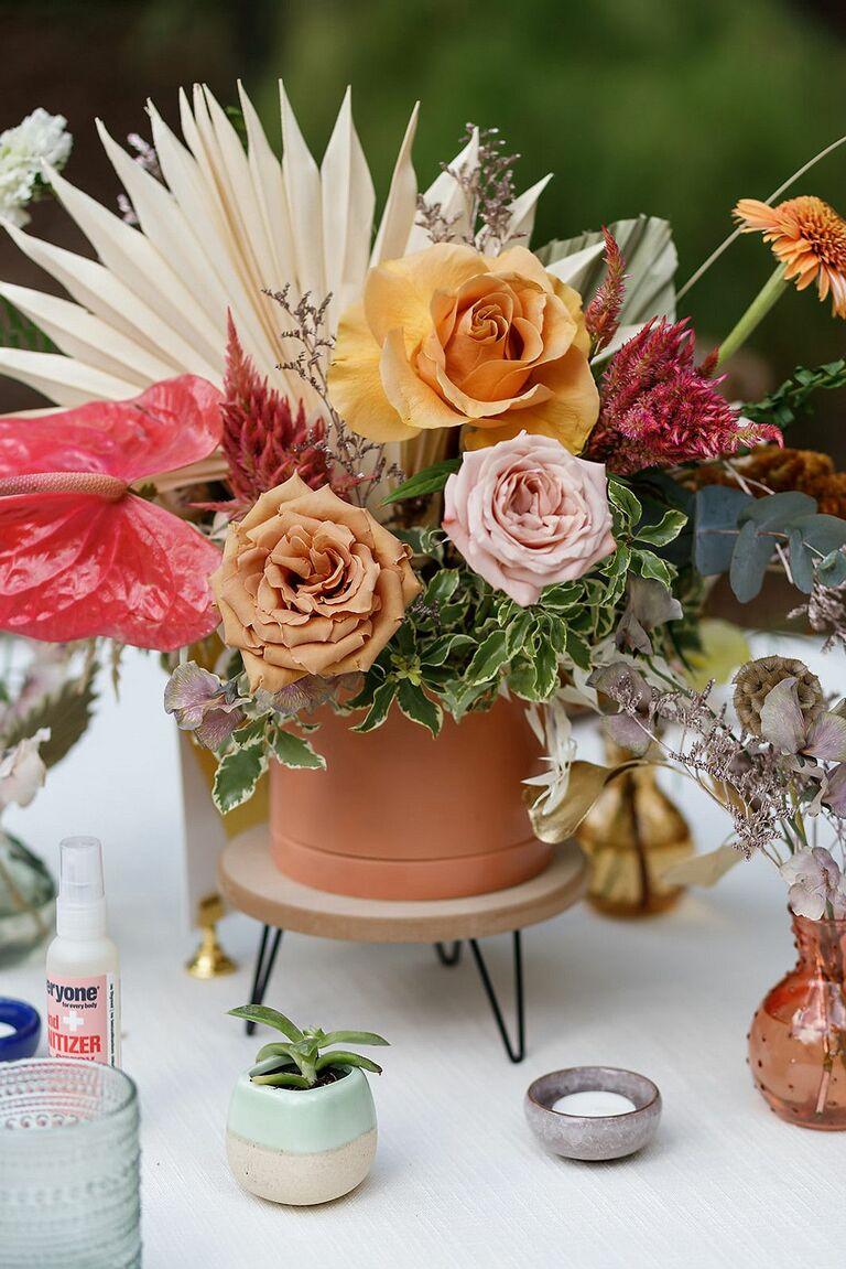 Rose and palm leaf floral arrangement on wood pedestal
