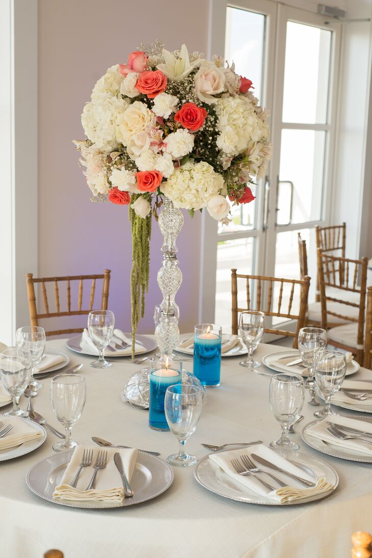 Tall flower arrangements of ivory and coral roses, hydrangeas, baby's breath and touches of hanging amaranthus, displayed in crystal vases, decorated the smaller, round dining tables. Floating candles in blue water brought in a beach-inspired touch.