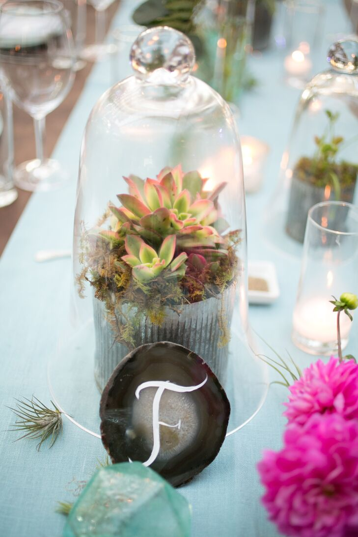 At each setting, soft green table runners provided a neutral backdrop for colorful pink centerpieces, tiny terrariums and geometric-patterned menus.