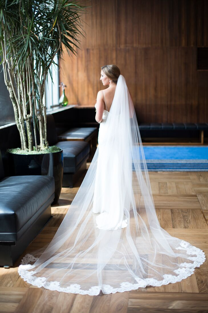 Wanting a dramatic look for the ceremony, Mari paired her open-back Nicole Miller dress with a timeless white veil. The cathedral-length accent definitely added a sense of elegance and glamour to her look by its sheer size. (Its classic lace trim also matched the white embroidery along her dress.)