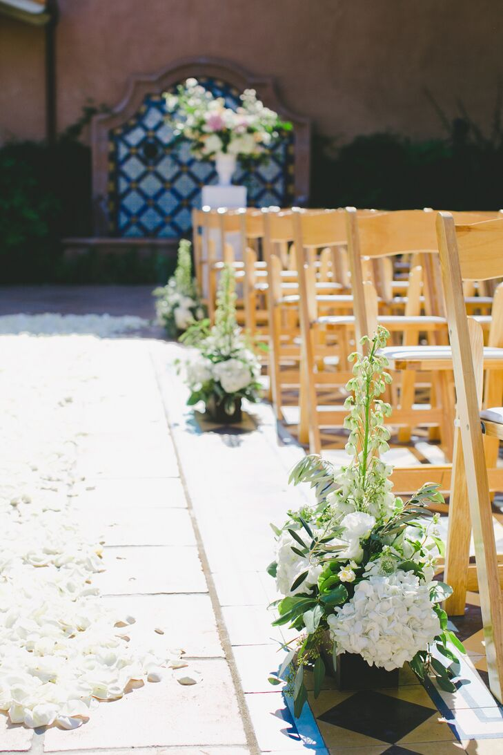 To bring the Rancho Valencia courtyard to life for the ceremony, Michelle Jacob lined the aisles with ivory rose petals and arrangements of white hydrangeas, delphiniums and textured greenery.