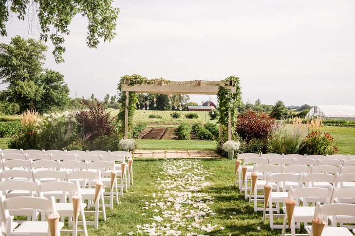 The couple's DIY outdoor ceremony took place at Heritage Prairie Farm in Elburn. To decorate the space, rose petals lined the aisle while wildflowers hung in flasks brought all the way from Thomas' dad's chemistry lab in Toronto.