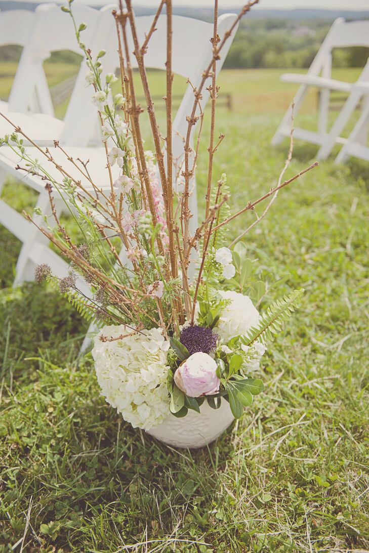 The simple grass aisle was decorated with vases of blooming branches, ferns and peonies.