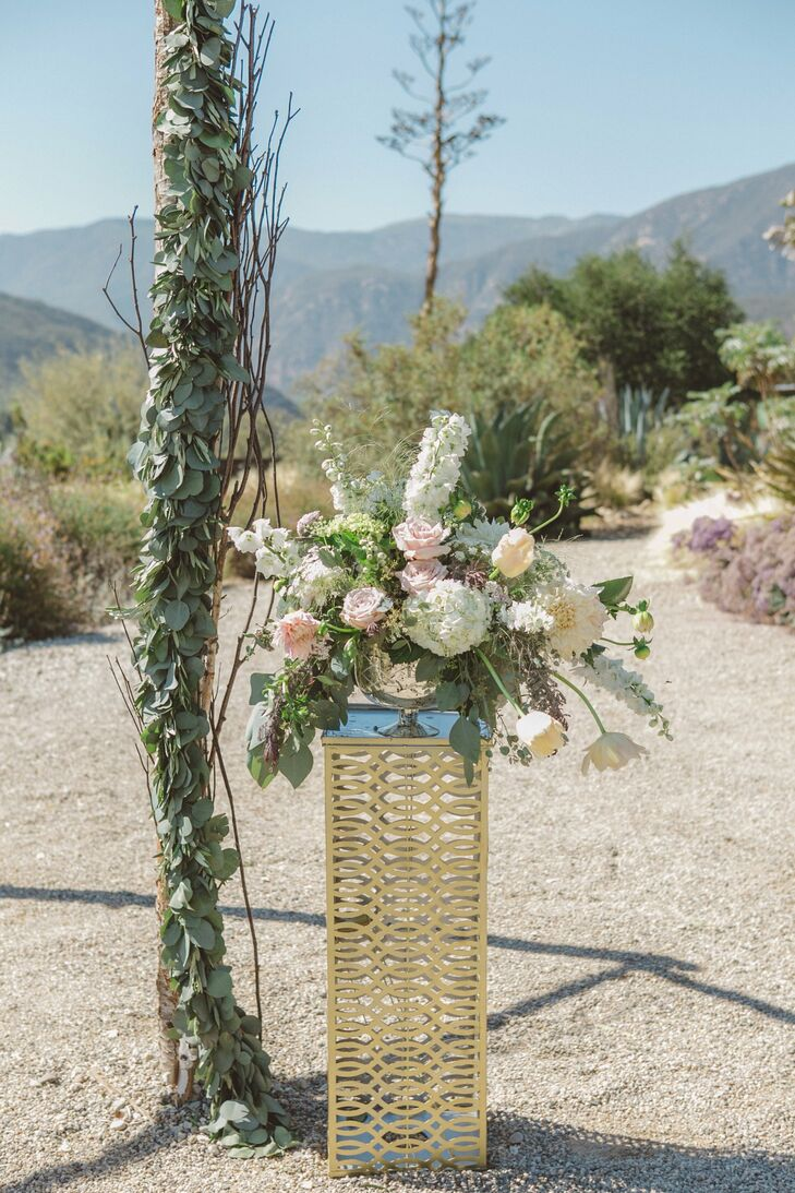 Keeping with the refined rustic theme, small-stemmed glass bowl vases sat atop stands made with a lacy bronze motif at the entrance to the outdoor ceremony.