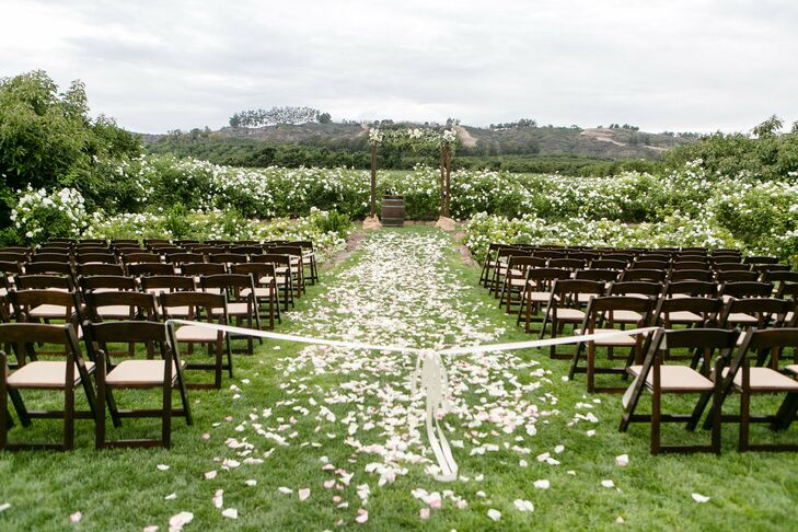 "Considering their mountainous backdrop and blueberry field ceremony, Allie and Adam opted to exchange vows under a simple wooden arch, draped with delicate blooms. A bow ""sealed the deal,"" as Allie puts it, above the petal-sprinkled aisle."