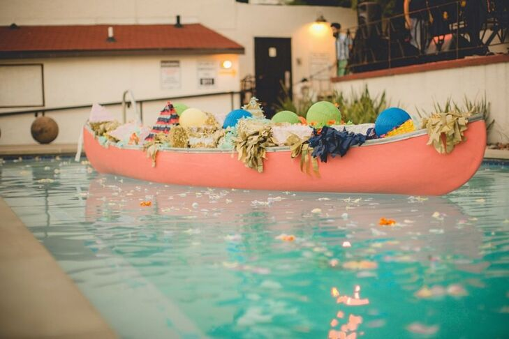 A canoe, filled with colorful paper poms and lanterns, floated in the swimming pool.