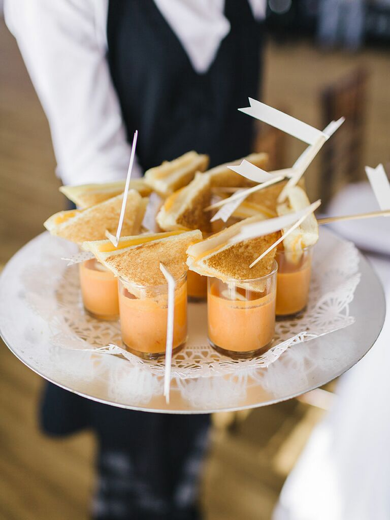 Mini grilled cheese slices with shots of tomato soup for a wedding reception snack
