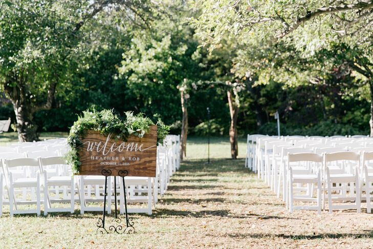 Lush greenery lined the wooden welcome sign, provided by Belovely. Romantic white folding chairs were situated in an apple orchard for the ceremony.
