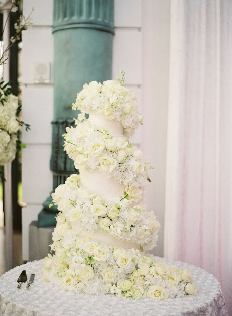 Ornate wedding cake covered in lots of fresh flowers
