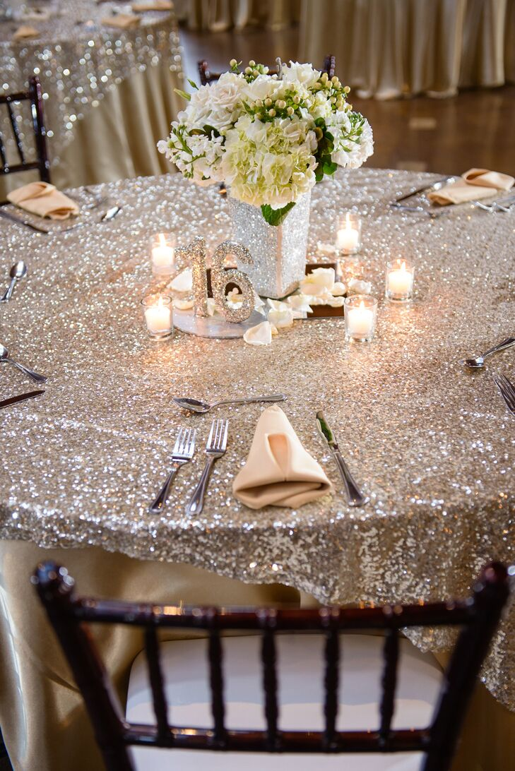 "The couple designed their silver glitzy silver decor around their New Year's Eve inspiration. Glitter accents popped against a black, white gold color palette and simple white flower arrangements filled sparkling vases. ""To pull the flowers in, we had some greenery in the arrangements brushed with gold paint,"" says Rachel."
