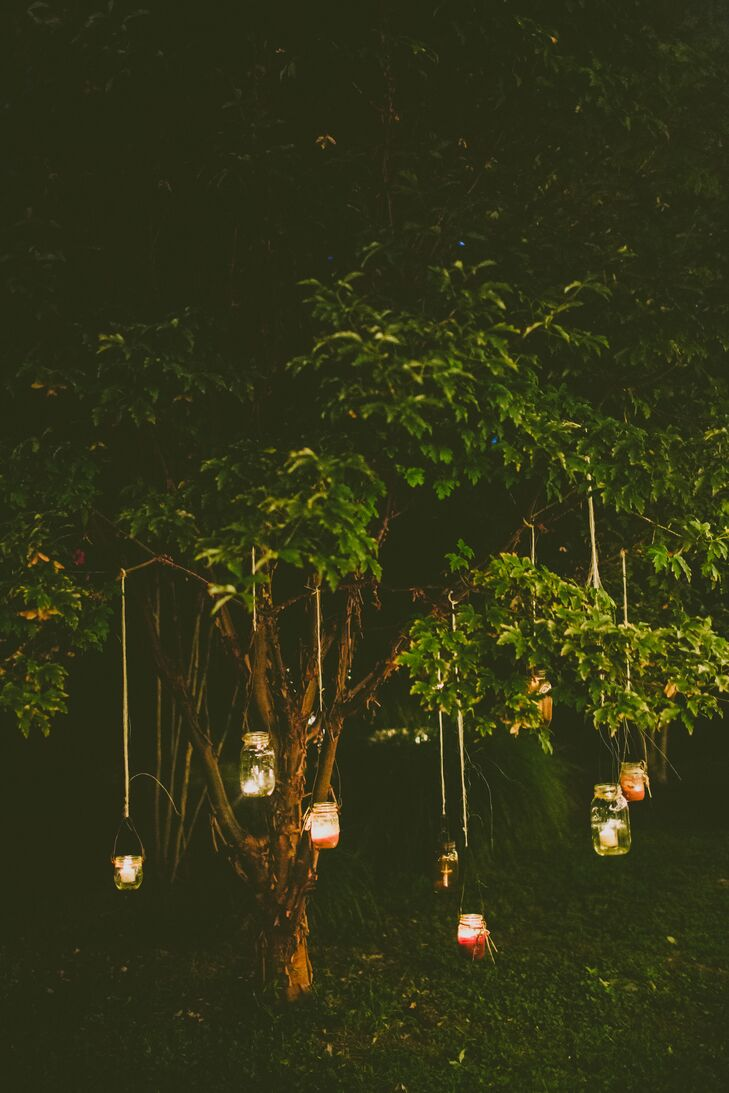 To create a magical yet natural look, candles in repurposed mason jars were lit and hung from trees surrounding the reception in Pittsboro, North Carolina. String lights were strung on the grapevines, and candles were placed on tree stumps.