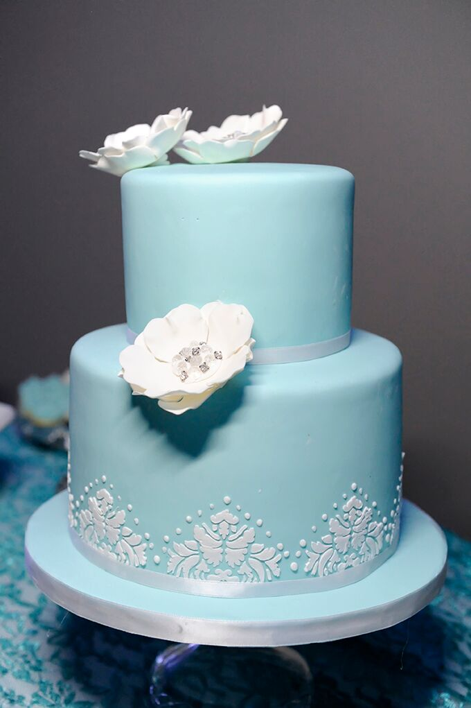 The couple's two tier turquoise cake was decorated with white sugar flowers.