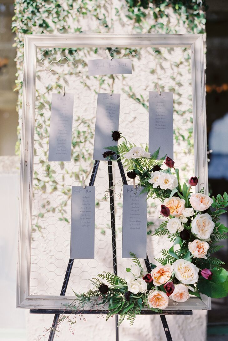 Seating assignments were posted on a clear piece of glass in a white frame, which was decorated with a swath of blush roses.