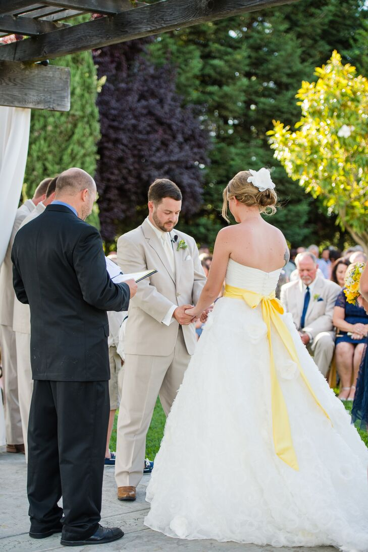 Claire and Nolan held hands in front of their officiant during their ceremony. Claire wore a strapless ivory wedding dress designed by Mori Lee, which was accented with a canary yellow sash that draped down the back. She had her hair styled into an updo with a white flower pinned to the top.