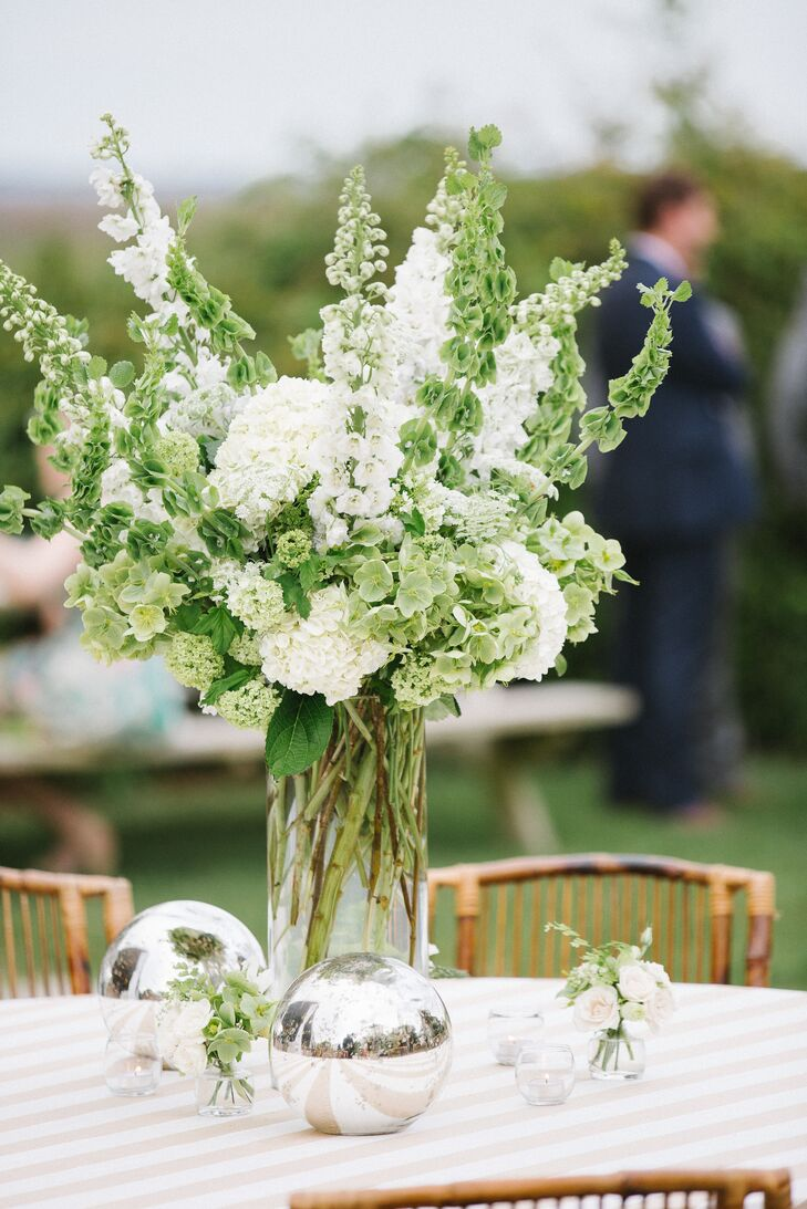 The tall dining table centerpieces of white and green flowers included Bells-of-Ireland, stock, hydrangeas and hellebores. Metallic modern spheres added a sophisticated touch.