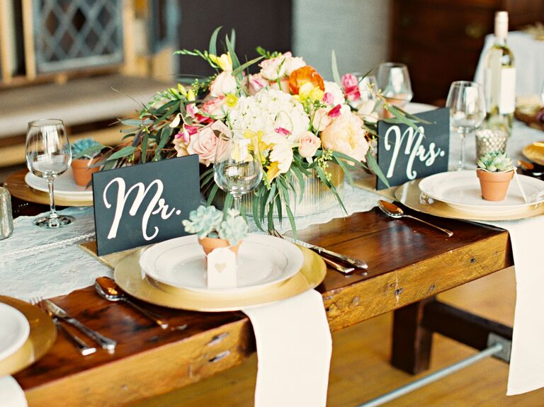 Mr. and Mrs. slate signs on rustic wooden reception table