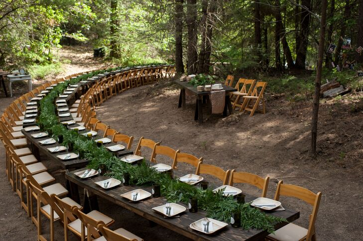 Victoria and David (with the help of family and friends) hand-built several wooden tables and placed them together to create a long, curving king's table for their 85 guests. A fern garland served as a verdant centerpiece.