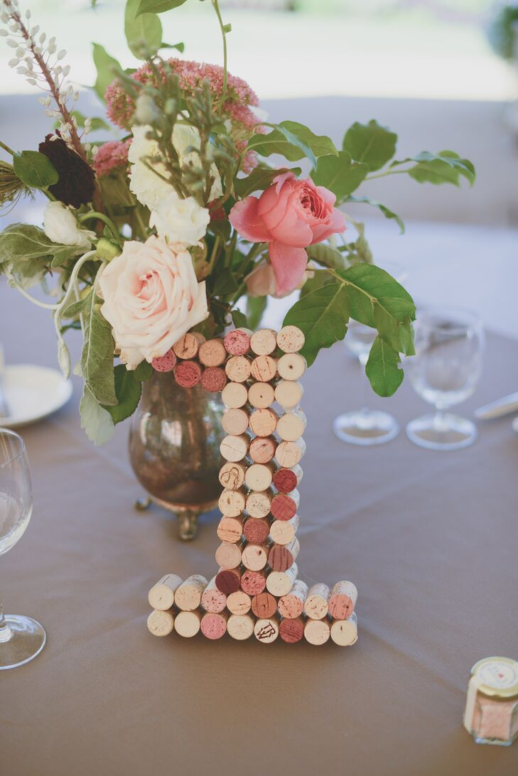 Table numbers made out of used wine corks rested against floral centerpieces on the tables at the reception.