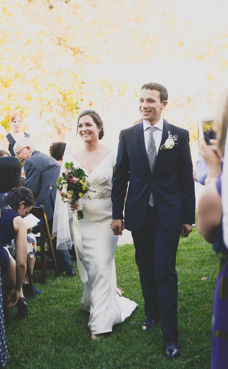 After exchanging vows under a chuppah built by the bride's father, the newly married couple walked up the grass aisle as guests happily looked on.