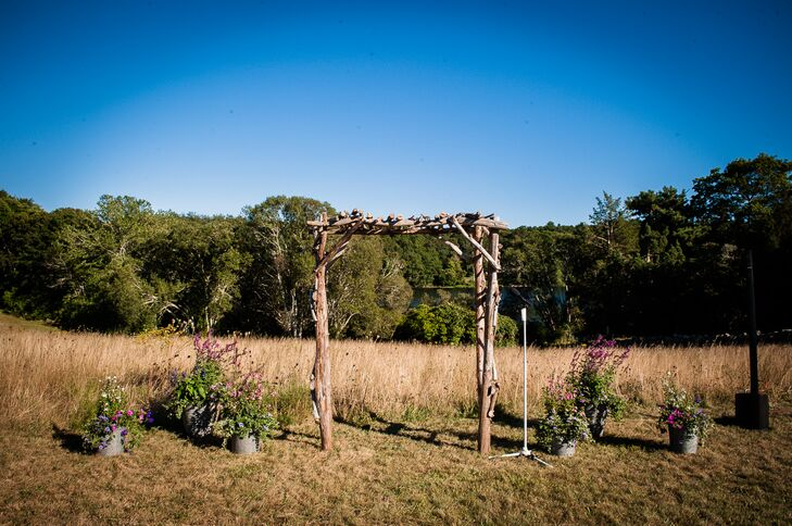 Kara and Justin said 'I do' under a wooden wedding arch on at the Bourne Farm in Falmouth, Massachusetts.