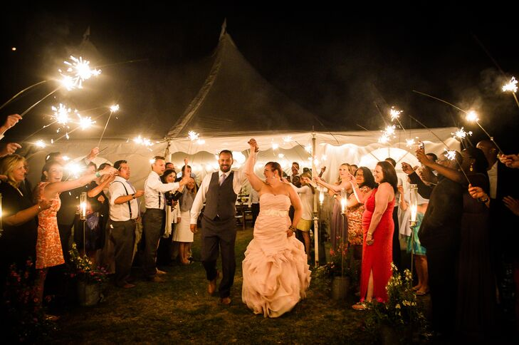 Kara and Justin exited their reception as newlyweds under the glow and crackle of their guests'  sparklers.